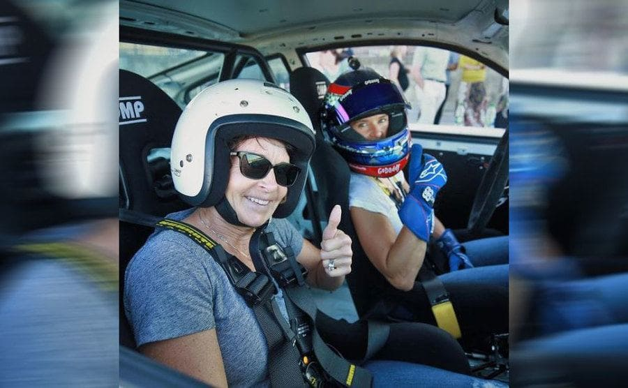 Danica and her mother holding their thumbs up for a photograph from inside of a racecar