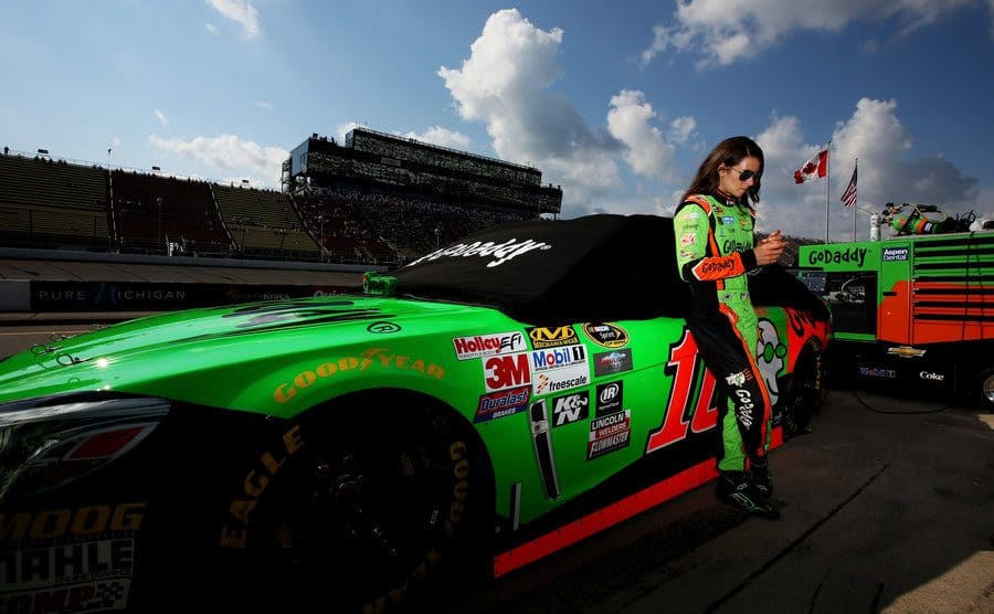 Danica Patrick posing while leaning against her race car