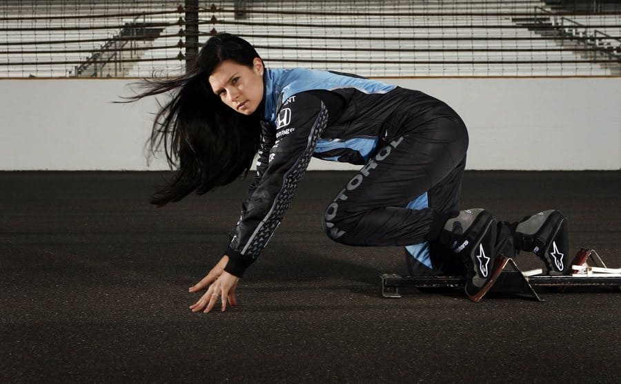 Danica Patrick posing in a sprinting position on the racetrack