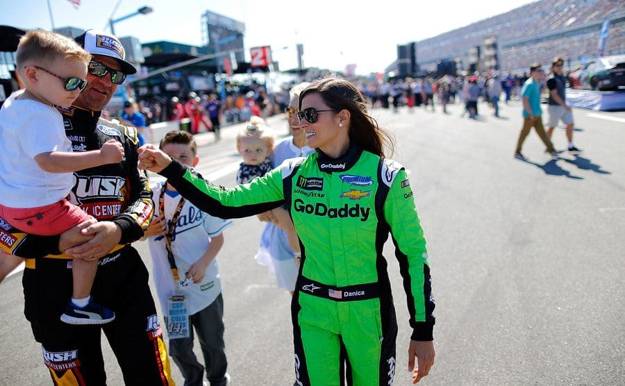 Danica Patrick fist-bumping a fellow racers son while walking on the track
