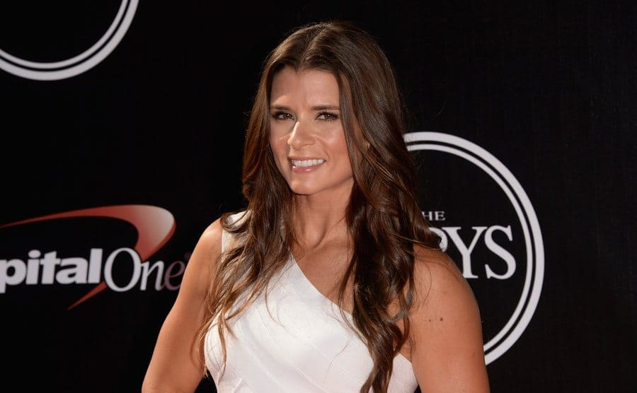 Danica Patrick on the red carpet in a white one-sleeve shirt