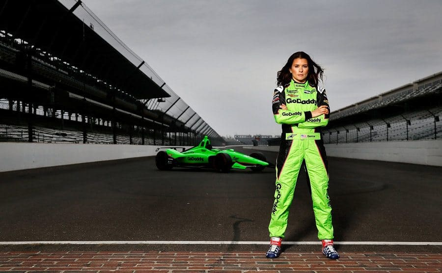 Danica Patrick posing by her car on the track