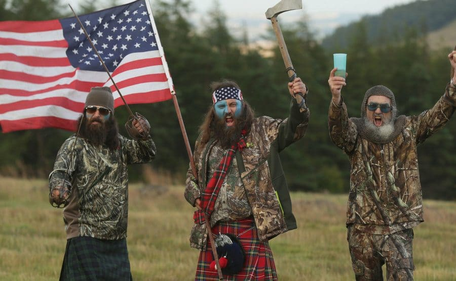 Members of Duck Dynasty waving an American flag.