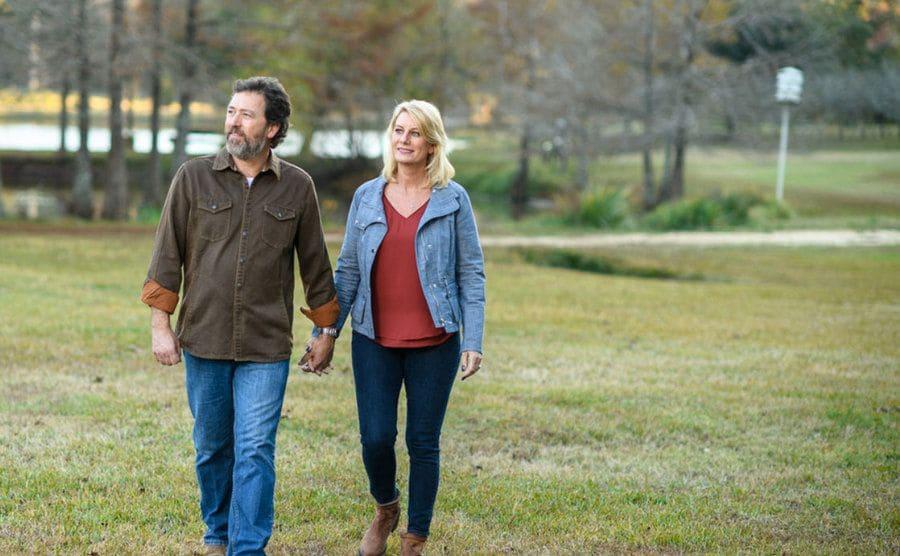 Alan and Lisa walking through a grassy field.