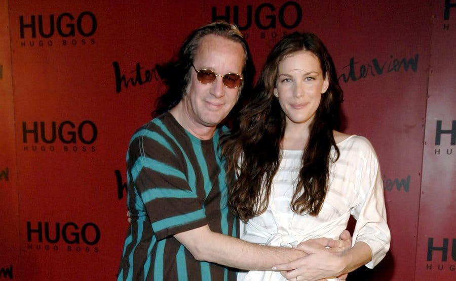 Todd Rundgren and Liv Tyler are posing on the red carpet for photos.