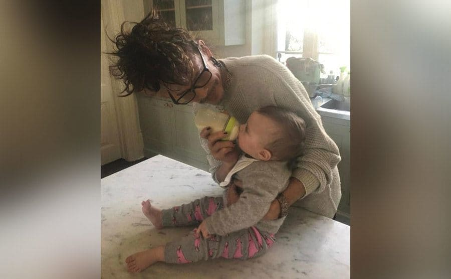 Steven Tyler is feeding his grandchild from a bottle.