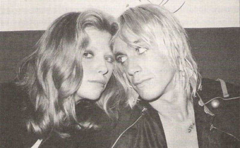 Bebe Buell and Iggy Pop are leaning their heads together.