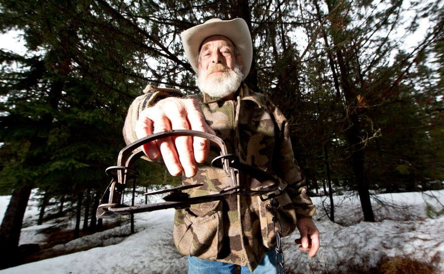 Tom Oar showing how dangerous life in the mountains can be by sticking his hand in a bear trap.