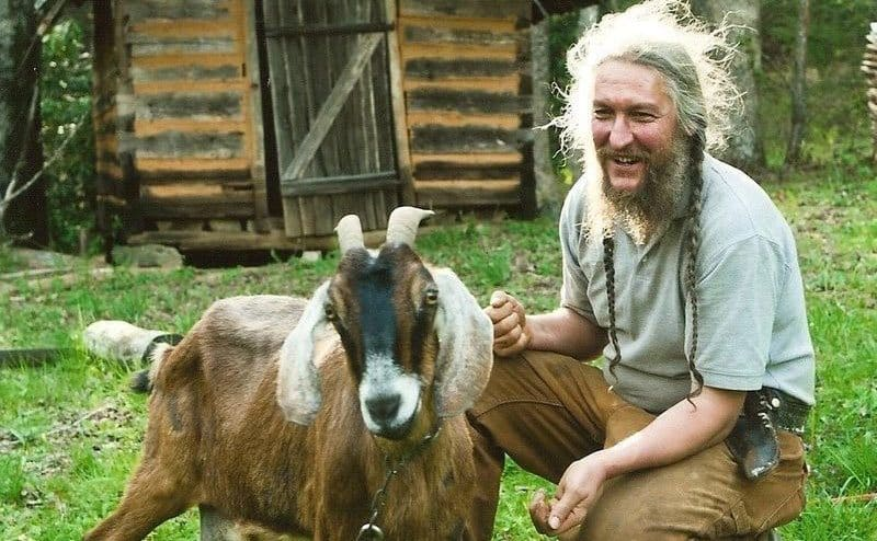 Eustace feeding a goat on his farm.