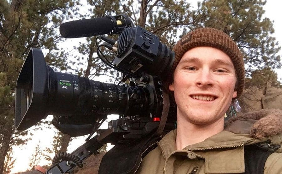 A young-looking cameraman taking a selfie while filming on location for Mountain Men.