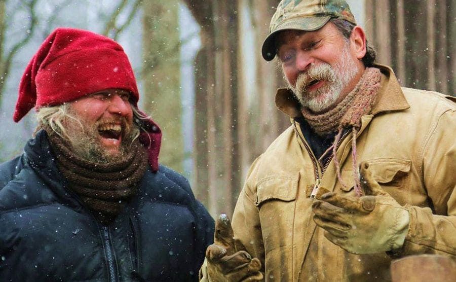 Preston Roberts and Eustace Conway are laughing out in the snow.