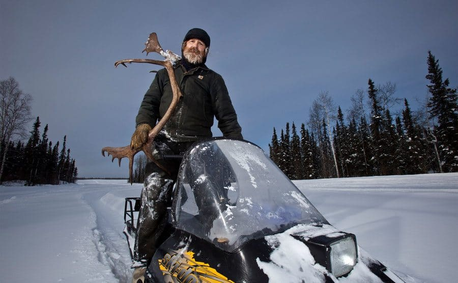 Marty riding his snowmobile while carrying moose antlers.