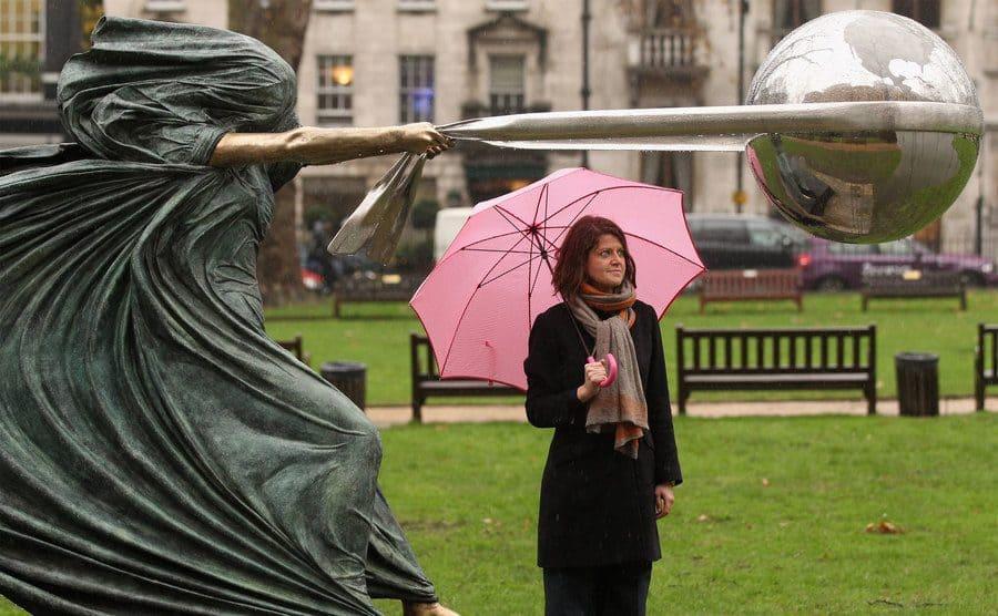"""Una mujer contempla la escultura """"La fuerza de la naturaleza"""", por el artista contemporáneo Lorenzo Quinn"""