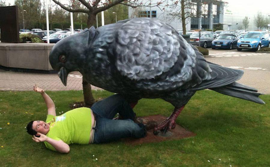 Divertida foto de chico posando junto a una escultura de paloma gigante