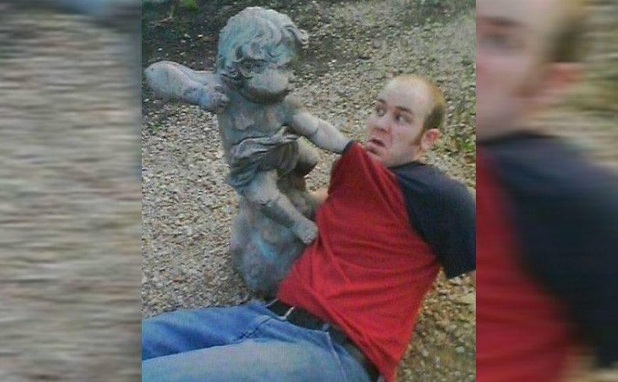 Graciosa imagen de chico posando junto a una estatua en forma de angelito enojado