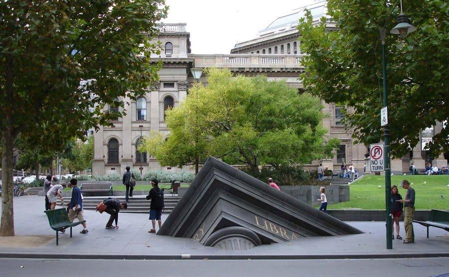 Escultura de edificio que se hunde fuera de la Biblioteca Estatal (Melbourne, Australia)