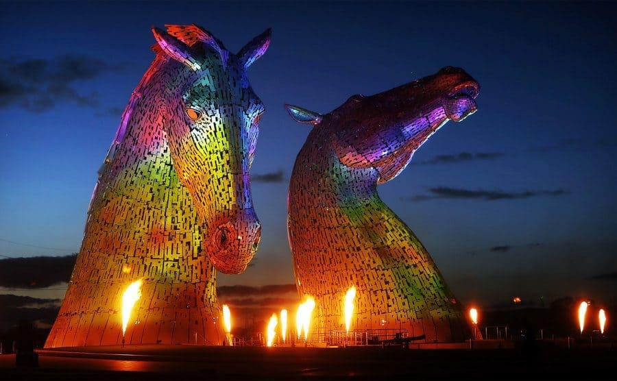 Esculturas de dos enormes cabezas de caballos iluminadas.