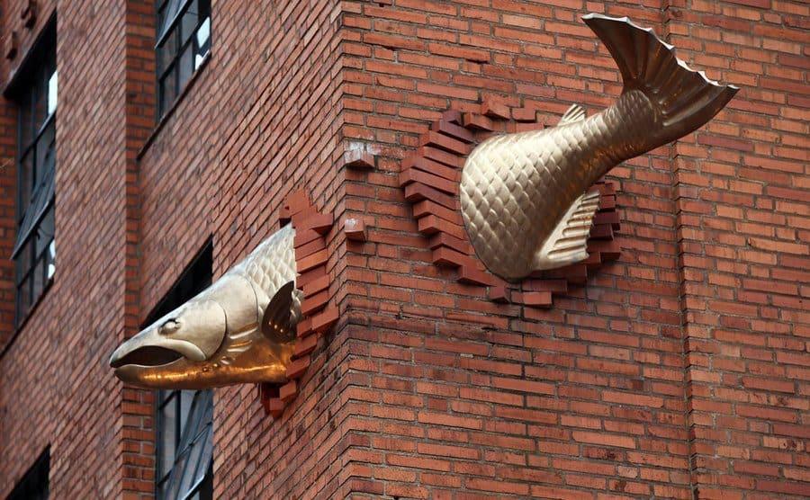 Una escultura de salmón atraviesa un edificio en Portland, Oregón