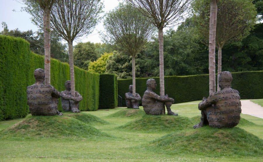 """""""Heart of Trees"""", esculturas de hombres con los brazos y las piernas enrollados alrededor de un tronco de árbol."""