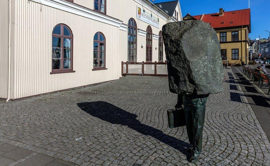 Escultura de un hombre con traje con la cabeza y hombros hundidos en una piedra sin esculpir.
