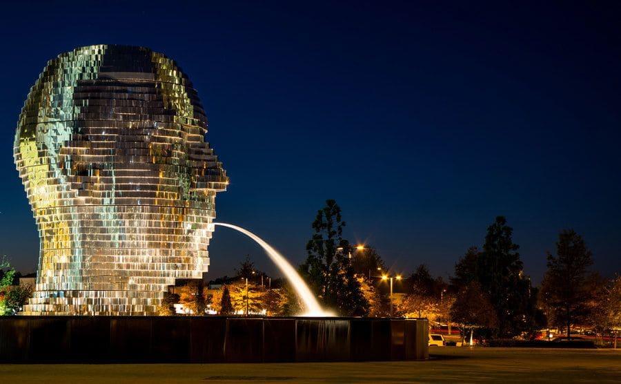 Enorme escultura de una cabeza gigante que arroja agua por la boca