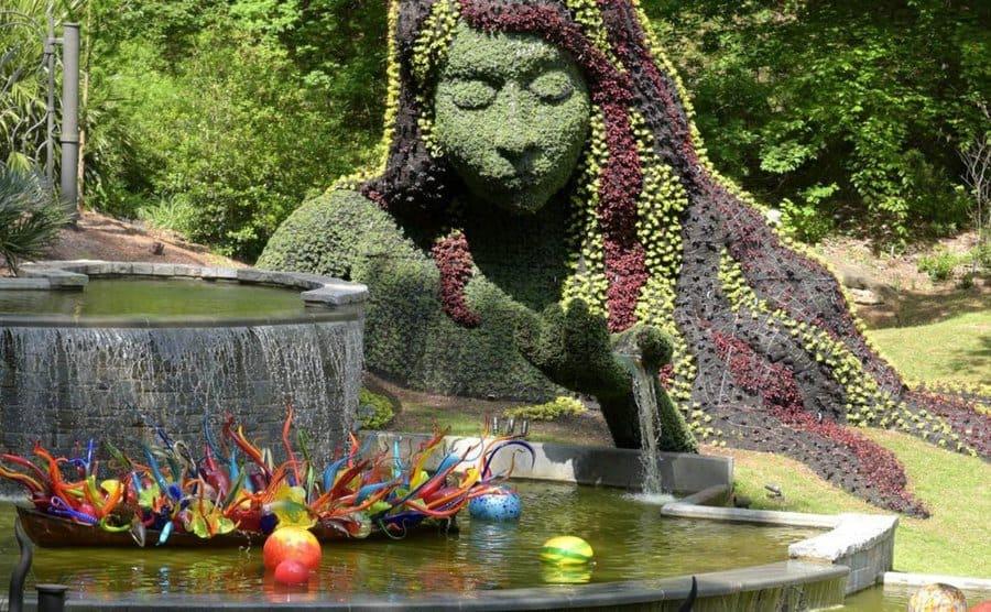 Escultura creada a base de flores y planta que evoca la madre naturaleza, en el parque bot+anico de Atlanta