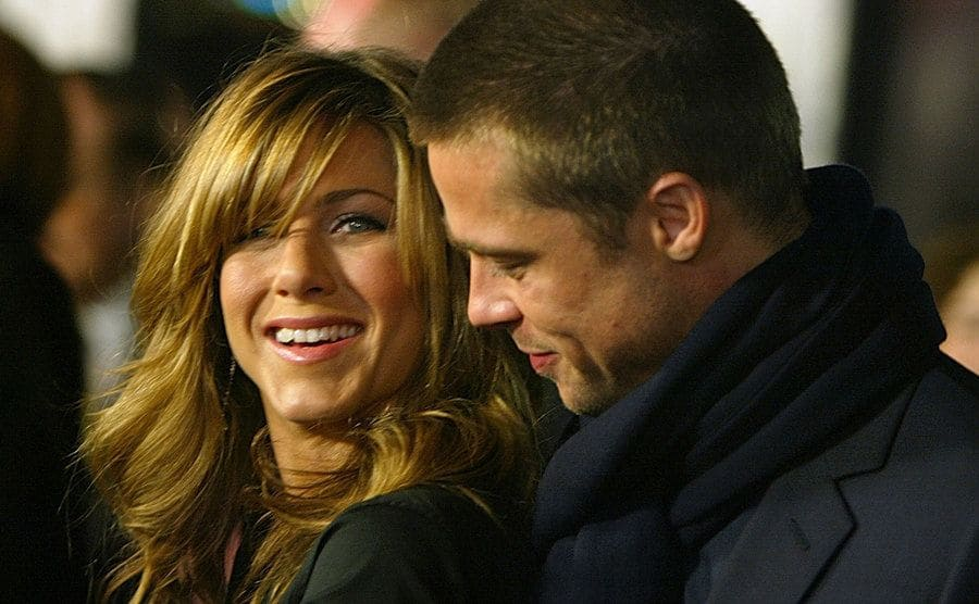 Jennifer Aniston smiling while Brad Pitt looks at her