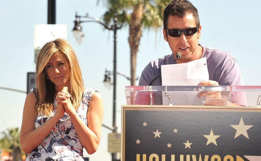 Jennifer Aniston tearing up while Adam Sandler reads behind a podium