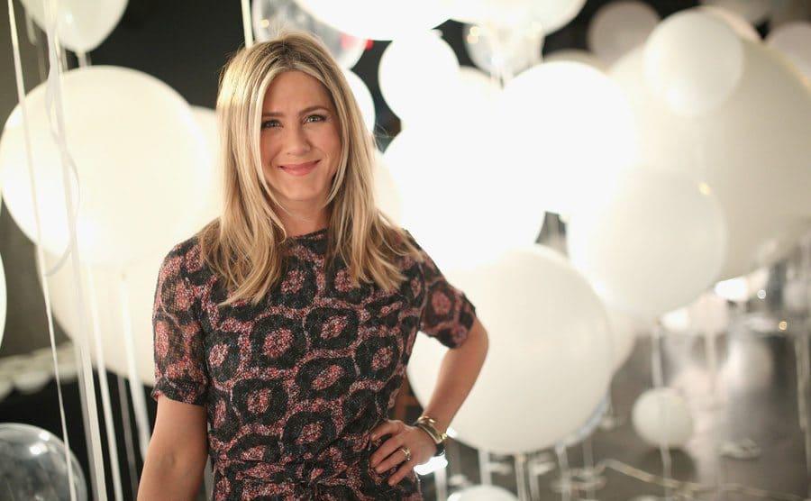 Jennifer Aniston posing in front of white balloons