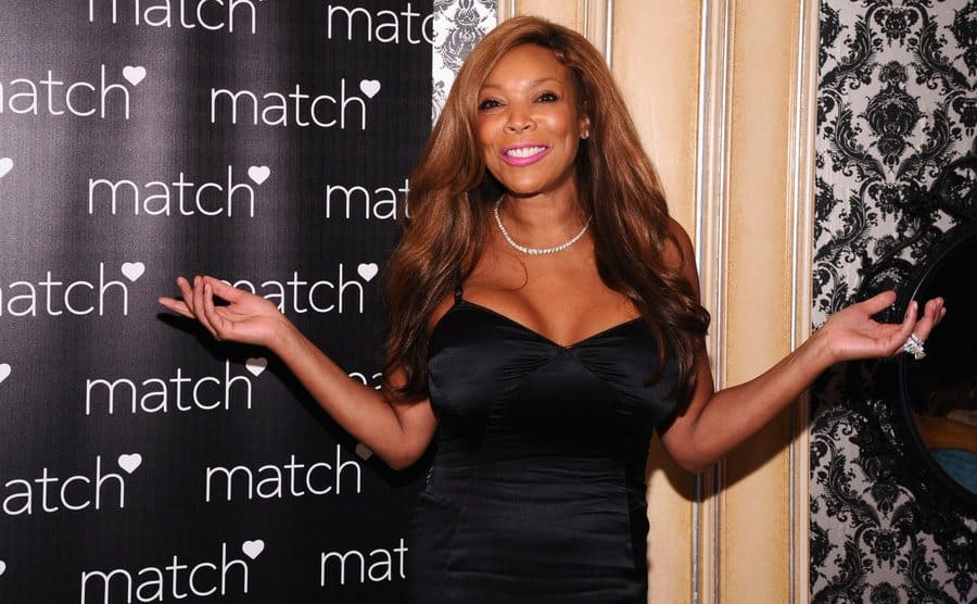 Wendy Williams posing with her arms spread on the red carpet