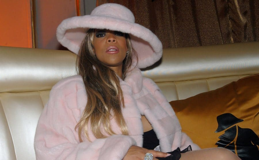 Wendy Williams in a pink fur coat with a matching hat sitting down at an event