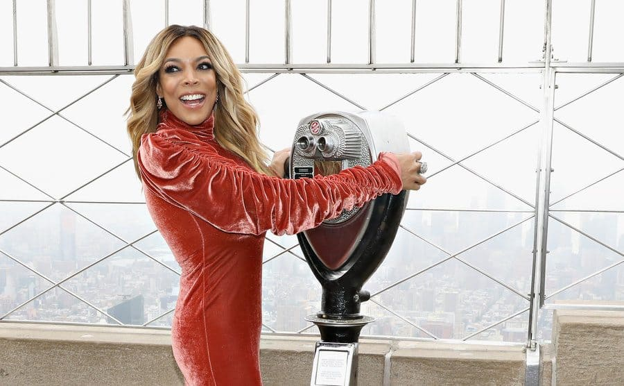 Wendy Williams posing for a photograph on the Empire State Buildings observation deck holding on to the binoculars