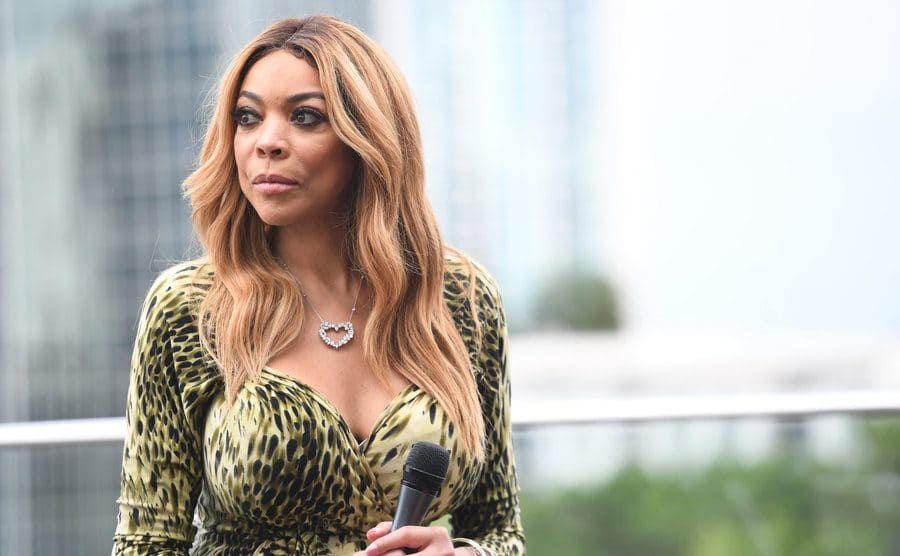 Wendy Williams standing on a balcony with a microphone in her hand, looking serious