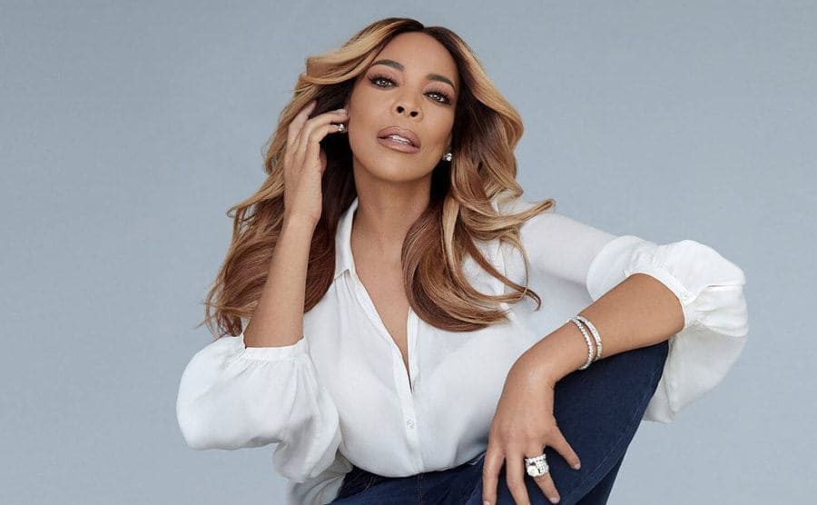 Wendy Williams poses for a portrait sitting on a plain white cube