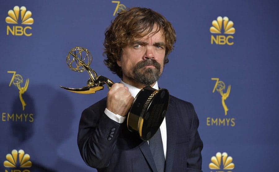 Peter Dinklage holding his Emmy Award on the red carpet