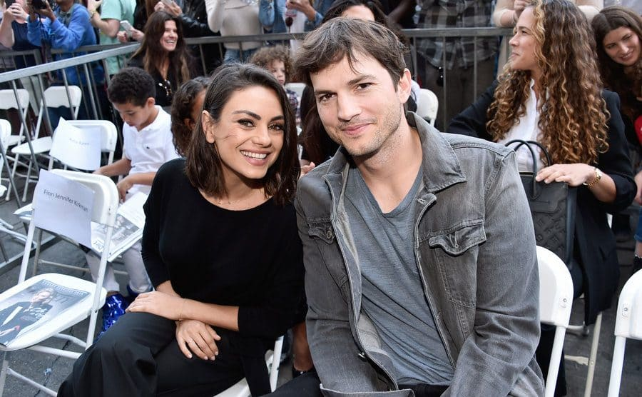 Mila Kunis and Ashton Kutcher sitting at an event in 2018