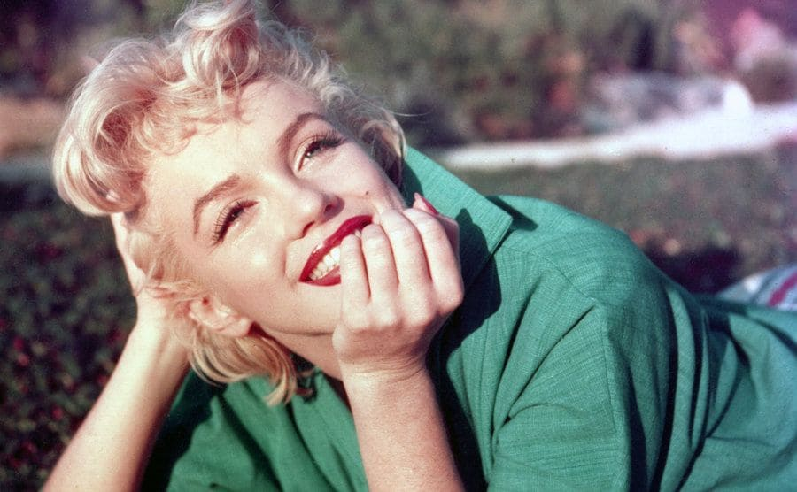 Marilyn Monroe lying in the grass posing for a portrait with bright red lipstick and a green outfit