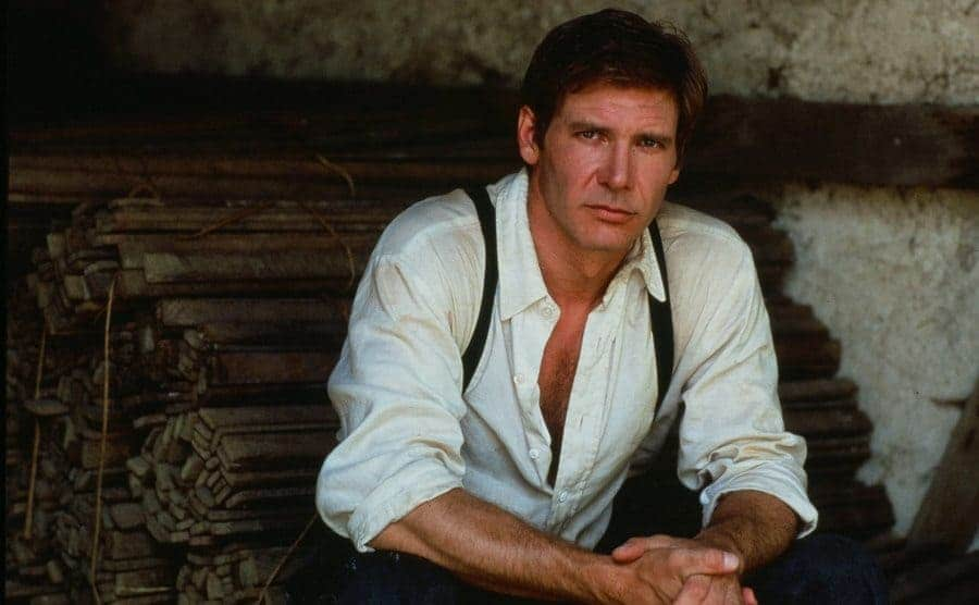 Harrison Ford sitting on stacks of thin wood
