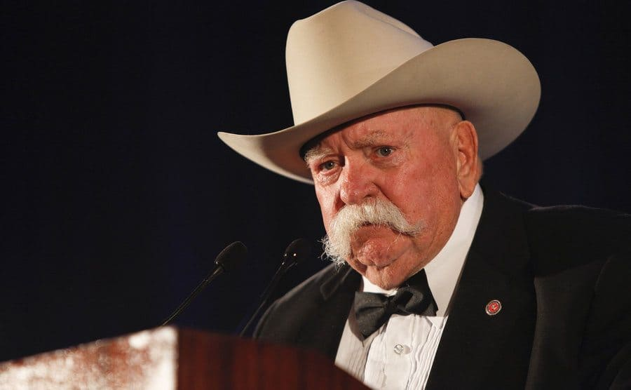 Wilford Brimley speaking behind a podium with a beige cowboy hat on