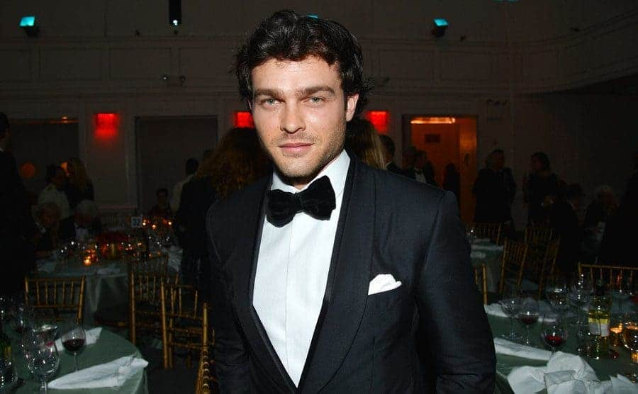 Alden Ehrenreich in a tuxedo standing between empty dinner tables at an event