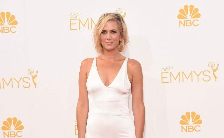 Kristen Wiig on the red carpet in a white v-neck gown