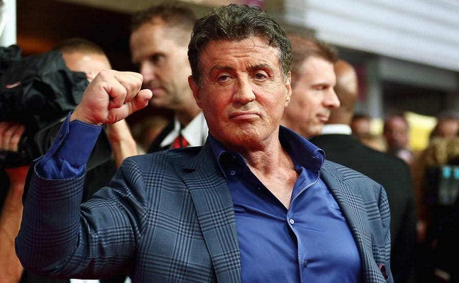 Sylvester Stallone holding up a clenched fist on the red carpet