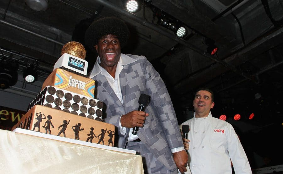 Magic Johnson standing next to a five-tiered cake which Buddy made for him