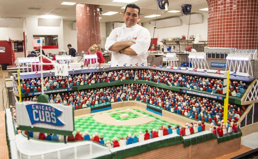 Buddy standing next to the Chicago Cubs cake