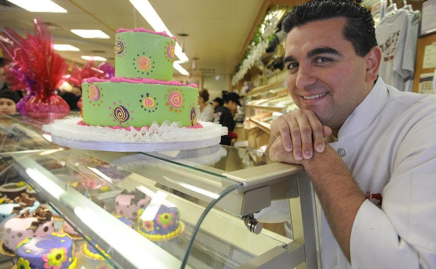 Buddy leaning on a display case with cakes inside and a two-layered cake on top