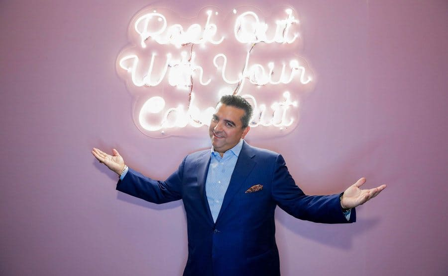 Buddy standing in front of a sign that says 'Rock out with your cake out'