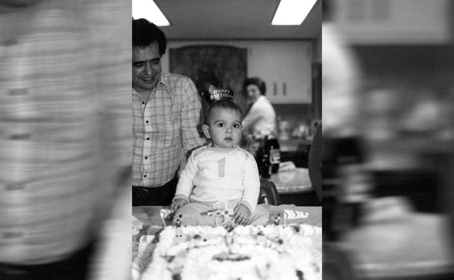 Buddy's father standing behind him on his first birthday