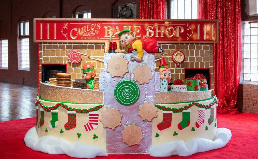 A cake in the shape of a brick oven with Carlo's Bake Shop written in the back and decorated for Christmas