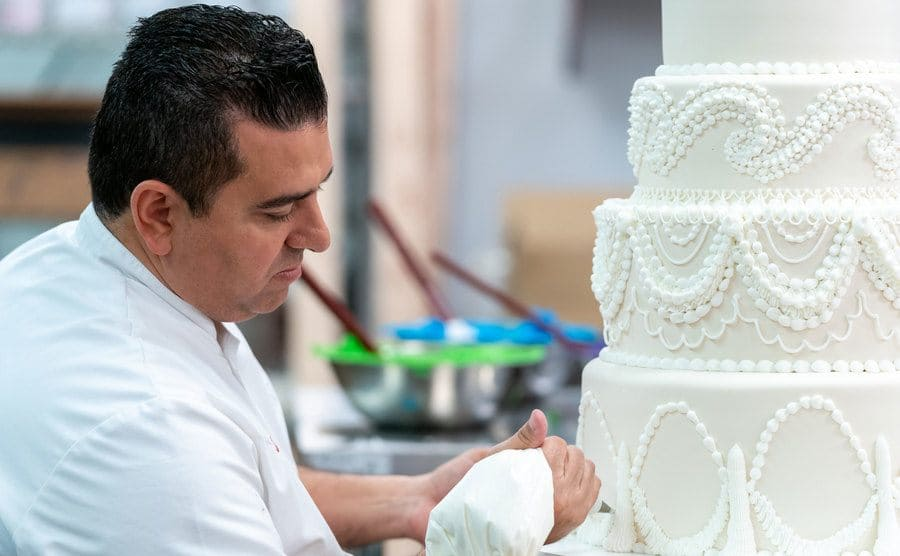 Buddy piping delicate designs into a white four-tiered wedding cake