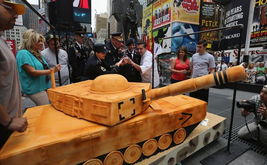 Buddy with soldiers taking a sword to the tank cake at Times Square